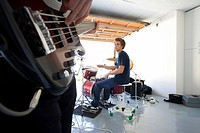 Teenage boy 16-18 playing drums in garage, looking at friend playing electric guitar in foreground