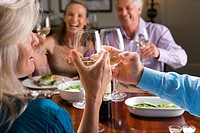 Two mature couples toasting wine glasses at dinner table, smiling