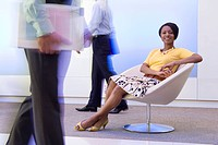 20's African American businesswoman sitting in chair in office with male colleagues walking by in foreground and background