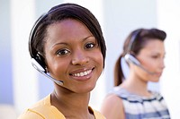 20's African American receptionist wearing communications headset smiling at camera with second receptionist in background