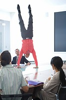 20's businessman doing handstand on board desk in meeting room watched by colleagues
