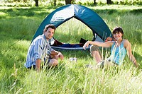 Young couple sitting near dome tent on camping trip in woodland clearing, smiling, side view, portrait