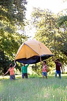 Four young adults carrying orange dome tent above heads on camping trip in woodland clearing