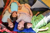 Family lying on sleeping bags in tent entrance, eyes closed, girl 8-10 smiling, portrait, overhead view
