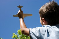 Boy 8-10 playing with toy aeroplane in summer garden, close-up, rear view, low angle view