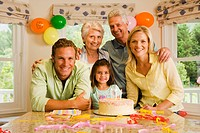 Three generation family celebrating birthday at home, girl 4-6 sitting beside birthday cake, smiling, portrait