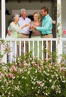 Family standing on veranda overlooking summer garden, making toast with champagne flutes, smiling