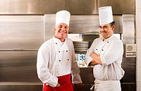 Two male chefs standing in commercial kitchen, smiling, portrait