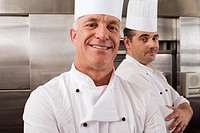 Two male chefs standing in commercial kitchen, arms folded, smiling, close-up, portrait