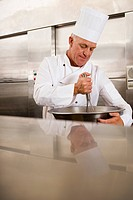 Mature male chef whisking ingredients in large bowl in commercial kitchen