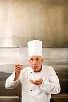 Chef holding large bowl in commercial kitchen, second chef tasting food sample with large spoon