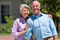 Senior couple standing on driveway, woman embracing man, smiling, portrait
