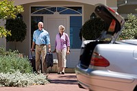 Senior couple leaving house with luggage in tow, smiling, portrait, parked car with open boot on driveway in foreground