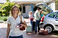 Family loading parked car boot on driveway, focus on mother standing with tickets in foreground, smiling, portrait