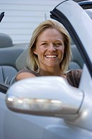 Woman sitting in driving seat of parked convertible car on driveway, smiling, portrait