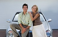 Couple leaning on bonnet of parked convertible car on driveway, smiling, front view, portrait