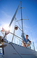 Man crouching on deck of moored sailing boat, holding rope lens flare