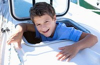 Boy 8-10 sticking head through open sailing boat cabin window, smiling, close-up, portrait