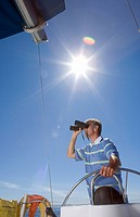 Man in striped blue polo shirt standing at helm of sailing boat out at sea, looking through binoculars, low angle view lens flare