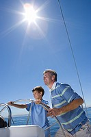Father and son 8-10 standing at helm of sailing boat out at sea, steering lens flare, tilt