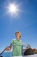 Woman in green polo shirt standing at helm of sailing boat out at sea, smiling, steering lens flare, tilt