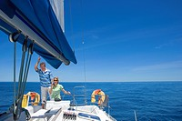 Couple standing at helm of sailing boat out to sea, holding hands, woman steering, man leaning on sail rigging, smiling