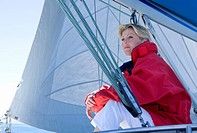 Woman in red jacket sitting on deck of sailing boat below sail, daydreaming, side view, low angle view