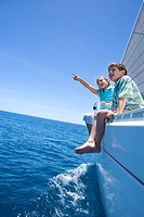 Boy and girl 8-10 sitting on deck of sailing boat out to sea, feet dangling over side, girl pointing, side view tilt