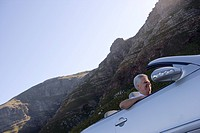 South Africa, Western Cape, senior man driving silver convertible car along mountain road, smiling, side view, low angle view tilt