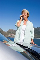 Senior woman standing beside parked convertible car on clifftop overlooking bay, using mobile phone, smiling