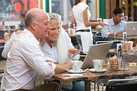 Mature couple sitting in cafe with coffees, looking at laptop, smiling