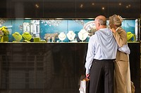 Mature couple looking at display window of jewelery store embracing, rear view