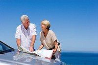 Senior couple standing beside bonnet of parked car on clifftop overlooking Atlantic Ocean, consulting map, smiling