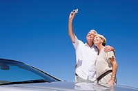 Senior couple standing beside parked car against clear blue sky, man taking self-portrait with digital camera, smiling
