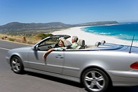 South Africa, Western Cape, senior couple driving in convertible car along coastal road, smiling, side view blurred motion