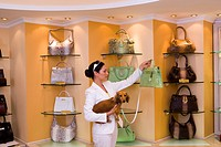 Young woman looking at green designer handbag in glamorous boutique, carrying dog, side view (thumbnail)