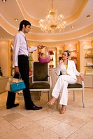 Young woman sitting on chair in glamorous boutique, male shop assistant showing her selection of designer handbags