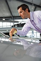 Car salesman polishing bonnet of new silver car with cloth in showroom surface level
