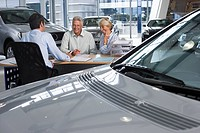 Car salesman and senior couple sitting at desk in large car showroom, new silver car in foreground