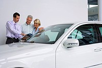 Car salesman showing senior couple new car in showroom, salesman pointing to brochure, smiling
