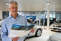Senior man standing in large car showroom, looking at brochure, smiling, portrait