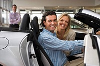 Car salesman standing in large car showroom, focus on couple sitting in driving seat of new silver convertible in foreground, smiling, side view, port...