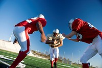 American football player running with ball at opposing team during competitive game surface level (thumbnail)