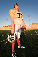 American football player standing on pitch, holding protective helmet, portrait