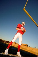 American football player, in red football strip and protective helmet, standing below goal post, holding ball, portrait surface level, tilt