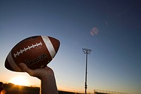 American football quarterback about to throw ball during competitive game on pitch at sunset, close-up, profile lens flare