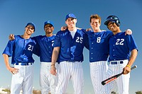 Baseball team, in blue uniforms, standing side by side, arms around each other, smiling, front view, portrait