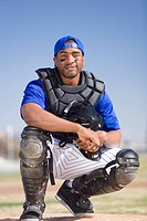 Baseball catcher wearing blue uniform, cap, protective glove and pads, crouching on pitch, smiling, front view, portrait