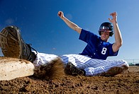 Baseball player, in blue uniform, sliding safely into base on pitch during competitive game surface level, blurred motion