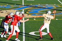 American football quarterback attempting to throw ball as opposing players close in during competitive game, side view